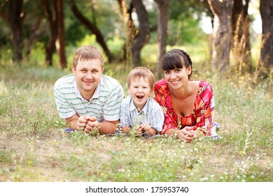 Father, mother and son in the park. Summer holiday. Happy family outdoors.