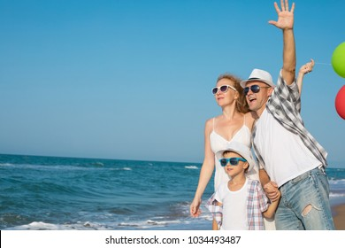 Father mother and son  playing on the beach at the day time. People having fun outdoors. Concept of summer vacation and friendly family.