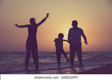 Father mother and son  playing on the beach at the sunset time. People having fun outdoors. Concept of summer vacation and friendly family.