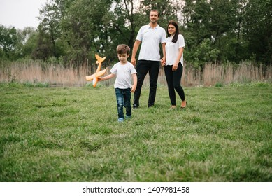 Father, mother and son playing with toy airplane in the park. friendly family. People having fun outdoors. Picture made on the background of the park and blue sky. concept of a happy family.