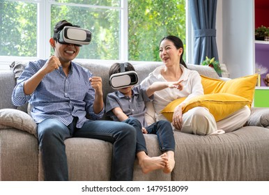 Father, mother and sons playing video games with virtual reality glasses - Father and sons  having fun with new technology console online