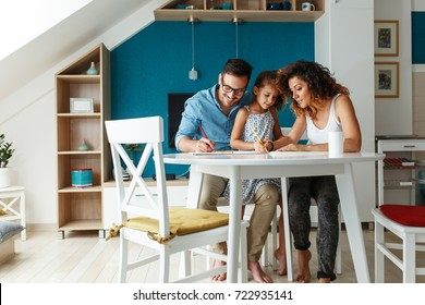 Father and mother teach daughter to draw.They sitting in living room and making fun.