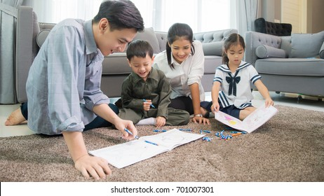 Father and mother Teaching children to do their homework at home ,and relax with they son to do home work by draw and paint, family , kid , education concept.