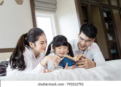 Father and mother Teaching children to do their homework with tablet at home,Asian family is happy.
