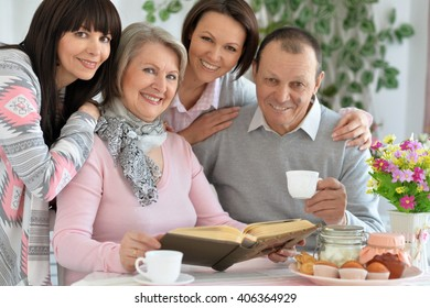 father, mother and two daughter together at the table drinking tea