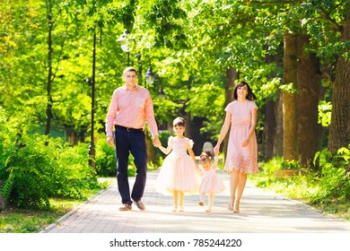 Father, mother and two daughters in the festive clothes are walking around the park in sunny weather