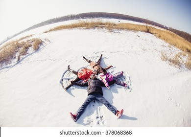 Father, mother and two daughters make circle in the snow