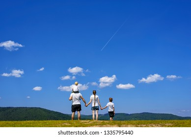 Father, mother and two little sons are standing on a green field on a background of wooded hills, blue sky and clouds. Family values.