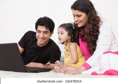 father and mother using laptop with the daughter on bed