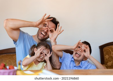 A father or nanny man is having fun with two small children, a girl and a boy, they are laughing and showing funny grimaces with their fingers close to their eyes as if they were glasses.
