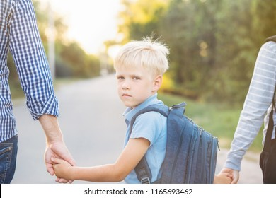 Father and older brother holding little son's hands. Little schoolboy with backpack going to school. Back to school concept.