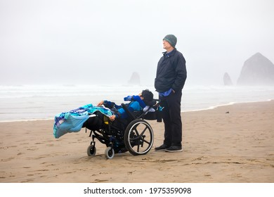 Father on beach with disabled  son in wheelchair on cold foggy day by ocean