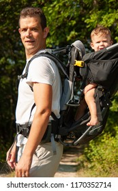 Father on a walk with kik in child carrier backpack .