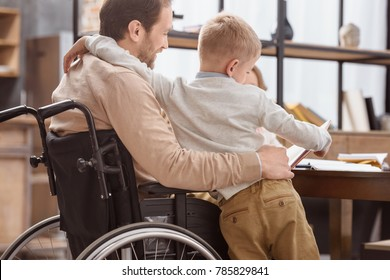 father on wheelchair teaching kids at home and hugging son