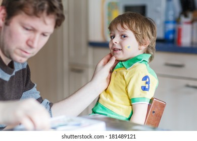 Father painting brazilian flag on face of little son for football or soccer game. Selective focus