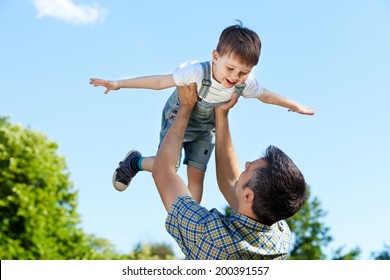 Father picking up smiling toddler in the park