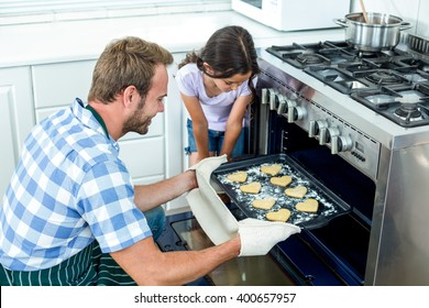 Father placing cookies tray in oven while daughter looking beside him