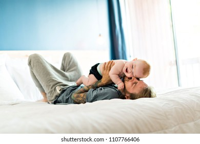 Father playing with adorable baby girl in bedroom