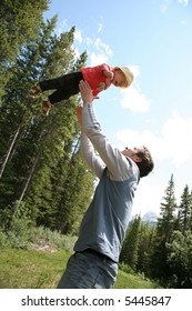 A father is playing with a child in the forest.