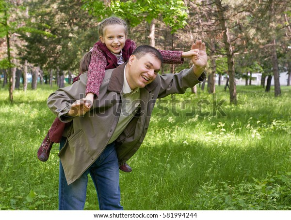 father playing with child girl in summer park, sunlight, green grass and trees