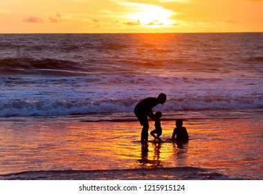 Father playing with children on beach by the oceanat at scenic sunset, Bali, Indonesia