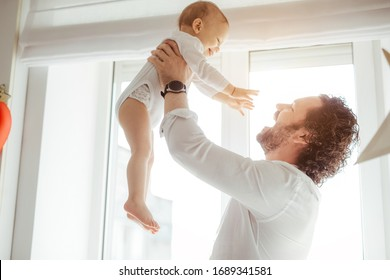 Father playing with cute newborn baby boy near the window in a sunny bright room. Loving father rising his son up and makes him smile. Enjoying sunny days at home. Perfect parenting relationship