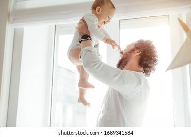 Vater spielt mit süßem Neugeborenen Jungen in der Nähe des Fensters in einem sonnigen hellen Raum. Der liebende Vater erhebt seinen Sohn und bringt ihn zum Lächeln. Genießen Sie sonnige Tage zu Hause. Perfekte Elternbeziehung