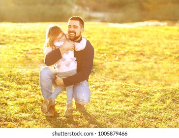 father playing with daughter in autumn park at sunset