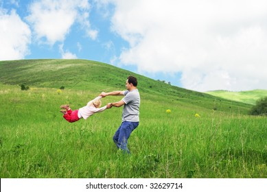 Father playing with daughter in meadow
