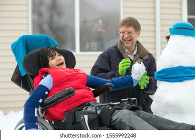 Father playing with disabled son in wheelchair  outdoors in the snow, throwing snowballs in winter outdoors
