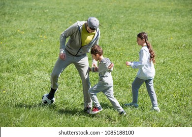 father playing football with daughter and son in park