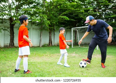 Father playing football for good relationship family. Asian people do activity.
