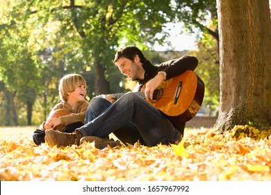 Father playing guitar for son outdoors in autumn