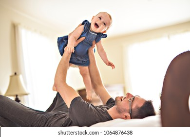 Father playing with her baby in the bedroom