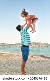 Father playing with his daughter on the evening beach during sunset. Mallorca, Spain. Daddy tosses up daughter
