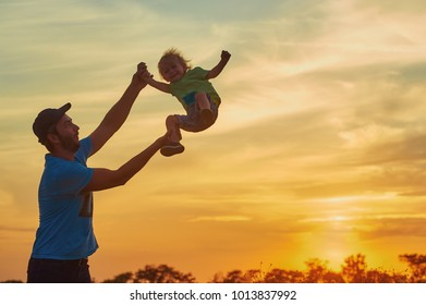 Father playing with his son at sunset