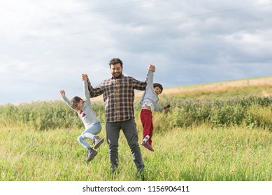 Father playing lifting his daughter and son in sporing day