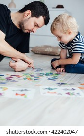 Father playing puzzle with son at home with copy space on the floor