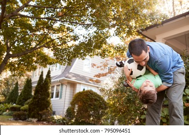 Father Playing With Soccer Ball In Garden With Son