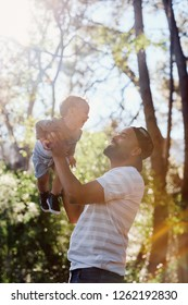 Father playing with son in forest with sun flare through the trees