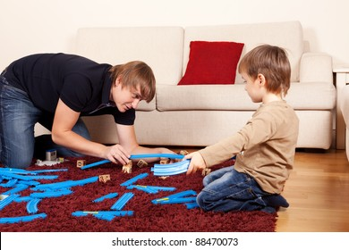 Father is playing with son in toy railroad
