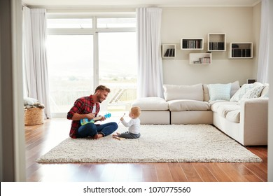 Father playing ukulele with young son in their sitting room