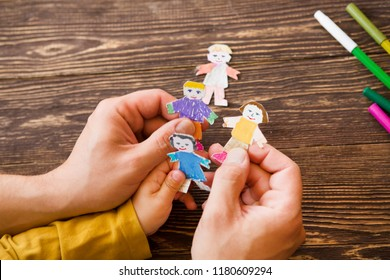 the father plays with the child in figures of people from paper on wooden background. Creative child play with craft.