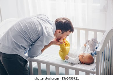 Father plays with his baby son and kissing baby in feet, while baby  lies in it's crib