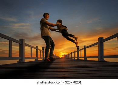 Father plays with his girl on the beach at sunset on wooded bridge