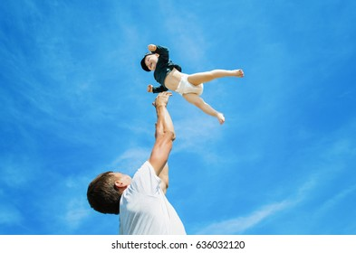 The father plays with his son throwing him in the blue sky. The concept of a friendly and happy family. Man throwing his child.