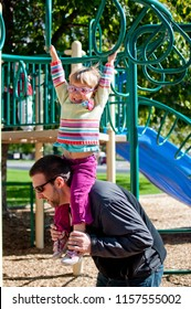 Father Plays At Playground With Daughter On Shoulders Helps Assists Her On Monkey Bars Equipment