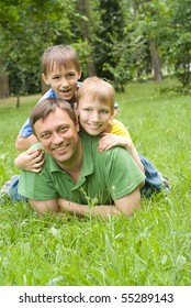 father  plays with young children outdoors