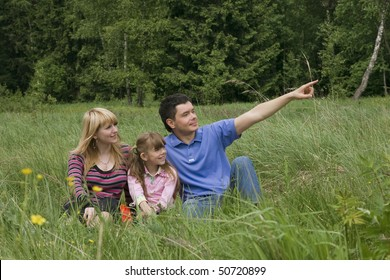 Father is pointing out something to his family while resting outdoor. Woman, man and child are resting outdoor.