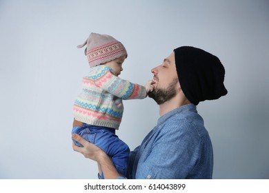 Father posing with cute baby daughter on light background